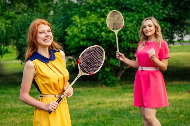 Two funny cheerful girlfriends beautiful young ginger redhead irish woman in a yellow dress and european blonde female person in a pink dress playing tennis badminton racket in the summer park
