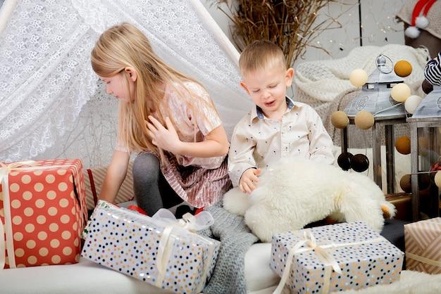 장식 된 집에서 크리스마스 선물 상자 사이에서 노는 두 재미 어린이 아이. 메리 크리스마스와 해피 홀리데이!