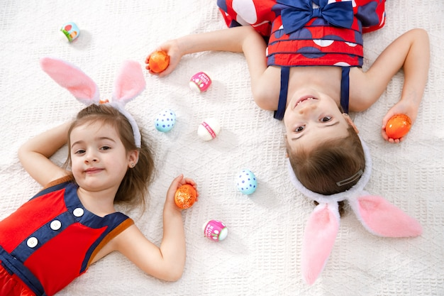 Two funny cute girls with easter eggs and bunny ears in a beautiful bright dress.
