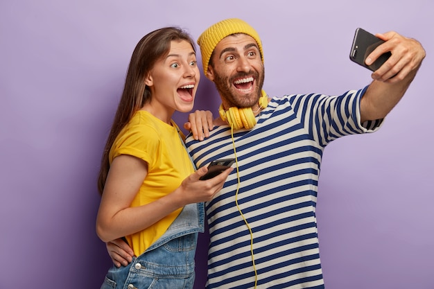 Two funny female and male friends take selfie on smartphone, have fun during recreation time, use modern mobile phone application