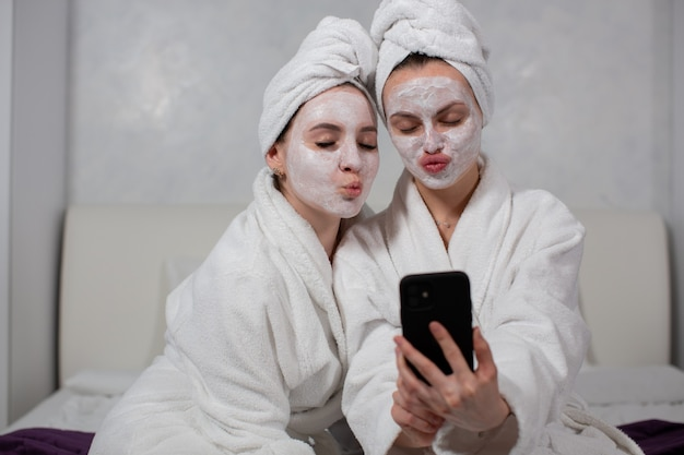 Two funny girl girlfriends in bathrobes, face masks and towels on their heads take selfies on the phone. high quality photo