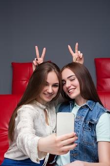 Две забавные подружки сидят на красном кожаном диване и делают селфи. женская дружба. досуг счастливых девушек