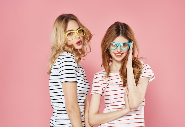 Two funny girlfriends with glasses fashionable clothes summer friendship