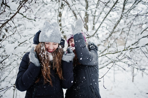 Two funny girls friends having fun at winter snowy day near snow covered trees.