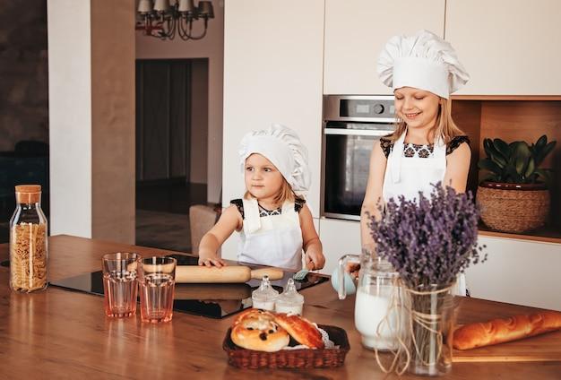 シェフの帽子とキッチンで遊んでいる白いエプロンを身に着けているキッチンで2人の面白い女の子