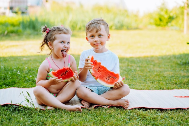 Two funny kids eat watermelon on back yard. kids eat fruit outdoors. healthy snack for children. toddlers show tongue to each other.