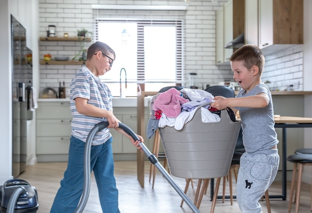 Two funny little brothers help with housework, vacuum and help mom with laundry.
