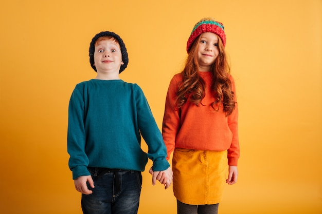 Two funny little children wearing warm hats
