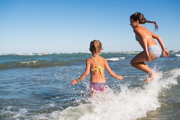두 명의 재미있는 어린 소녀가 시끄러운 바다 파도에 뛰어 들고 햇살이 내리는 따뜻한 여름날 오랫동안 기다려온 휴가를 즐기십시오. 바다 휴가의 개념과 아이들과 함께 여행
