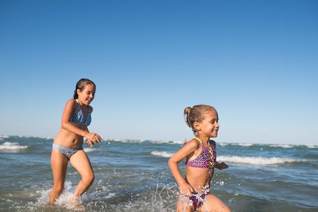 두 명의 재미있는 어린 소녀가 시끄러운 바다 파도에 뛰어들고 화창한 따뜻한 여름날 대망의 휴가를 즐깁니다. 바다 휴가 및 아이들과의 여행의 개념