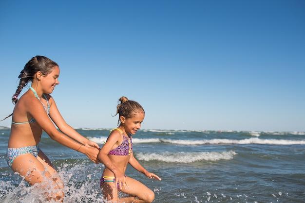 두 명의 재미있는 어린 소녀가 시끄러운 바다 파도에 뛰어 들고 햇볕이 잘 드는 따뜻한 여름날 오랫동안 기다려온 휴가를 즐기십시오.