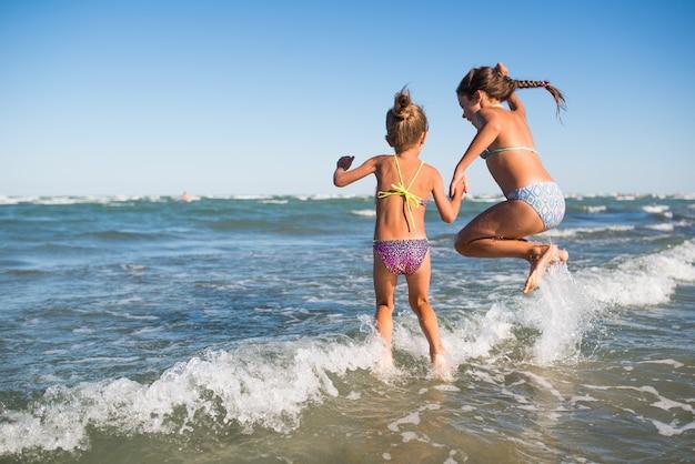 두 명의 재미있는 어린 소녀가 시끄러운 바다 파도에 뛰어 들고 햇볕이 잘 드는 따뜻한 여름날에 오랫동안 기다려온 휴가를 즐기십시오.