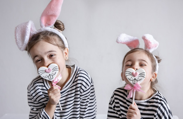 Two funny little sisters are posing with easter gingerbread in the form of bunny faces.