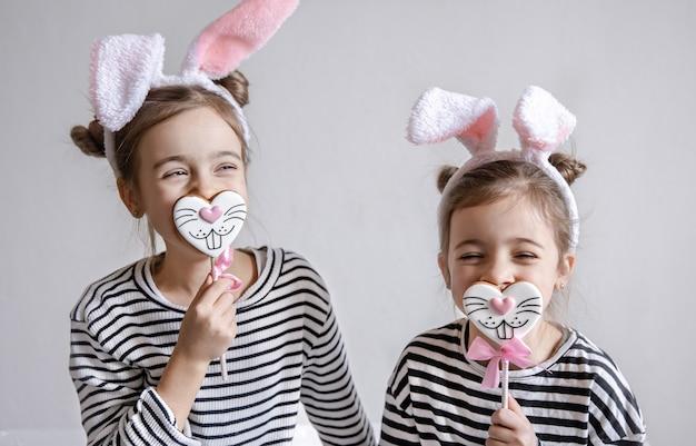 Две забавные сестренки позируют с пасхальными пряниками в виде кроличьих мордашек