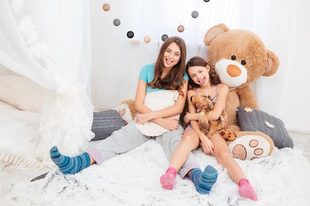Две забавные милые сестры сидят и показывают языки в детской комнате
