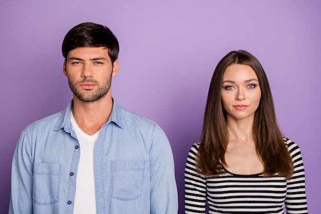 Two funny people couple not smiling looking seriously not talking to each other, wear stylish casual outfit isolated pastel purple color wall