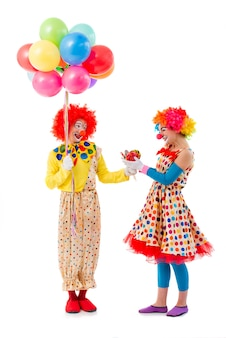 Two funny playful clowns looking at each other and smiling.