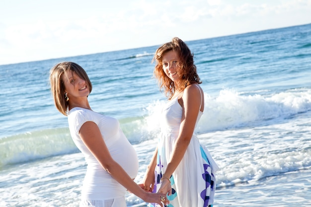 Two funny sisters on the beach.