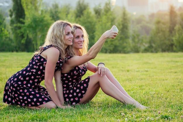 두 명의 재미있는 자매 쌍둥이 아름다운 곱슬곱슬한 금발의 행복한 젊은 이빨 미소 여성은 세련된 드레스를 입고 여름 공원 일몰 광선 필드 배경에서 재미 있고 전화로 셀카를 만듭니다.