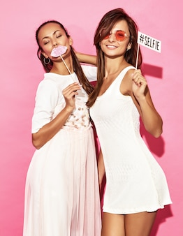 Two funny smiling women with big lips and selfie on stick. smart and beauty concept. joyful sexy young models ready for party. hot women isolated on pink wall. positive female