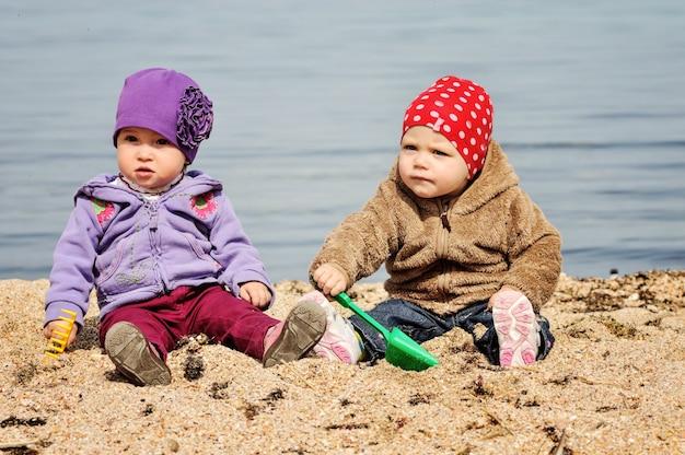 ビーチで砂を遊んでいる2人の面白い幼児