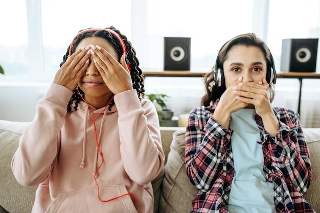2 人の面白い女性が冗談を言い、家で音楽を聴いています。イヤホンをしたかわいいガールフレンドが部屋でくつろぎ、音の愛好家がソファで休んで、女性の友達が一緒にレジャーをする
