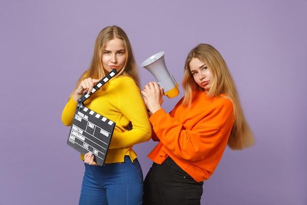 Две забавные молодые блондинки сестры-близнецы, держащие классическую черную пленку, делая с 'хлопушкой', кричат на мегафон, изолированном на фиолетовой синей стене. концепция семейного образа жизни людей. .
