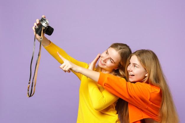 Две забавные молодые блондинки сестры-близнецы в красочной одежде делают селфи на ретро-винтажной фотоаппарате, изолированной на фиолетовой синей стене. концепция семейного образа жизни людей.