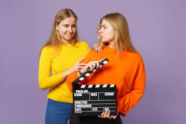 보라색 파란색 벽에 절연 clapperboard 만들기 클래식 블랙 영화를 들고 화려한 옷을 입고 두 재미 젊은 금발 쌍둥이 자매 여자. 사람들이 가족 라이프 스타일 개념. .