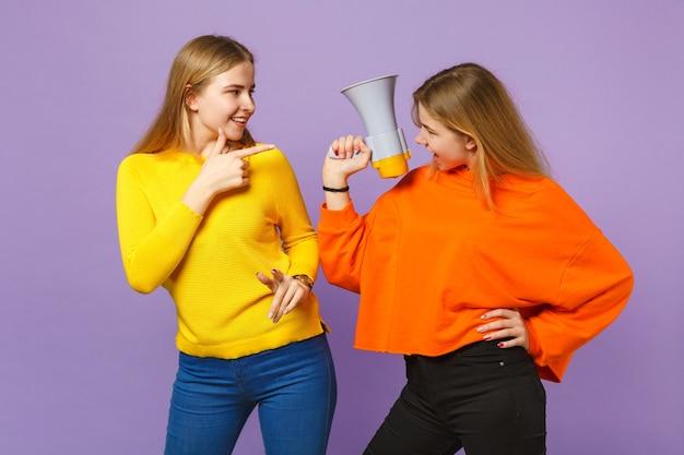 パステルバイオレットブルーの壁に分離されたメガホンで人差し指の悲鳴を指すカラフルな服を着た2人の面白い若いブロンドの双子の姉妹の女の子。人々の家族のライフスタイルの概念。
