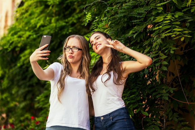 Two funny young girls are taking selfie photos on the smartphone near the wall of greenery