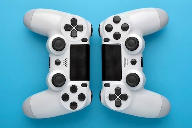 Two game controllers on blue background. game concept. competition concept. top view.
