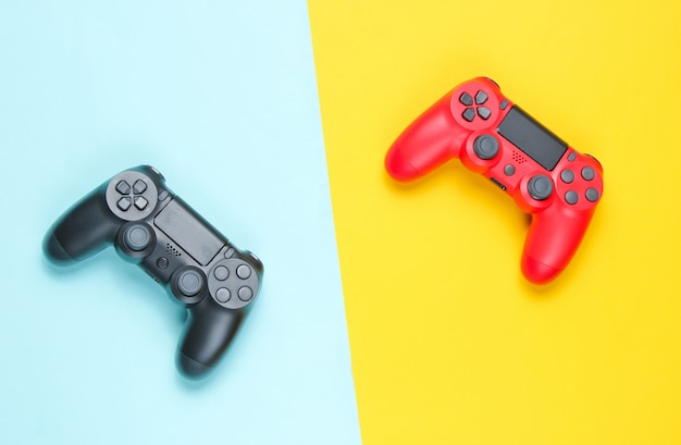 Two gamepad on a colored paper background.