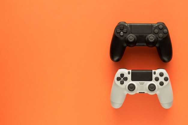 Two gamepads on a orange table and copy space