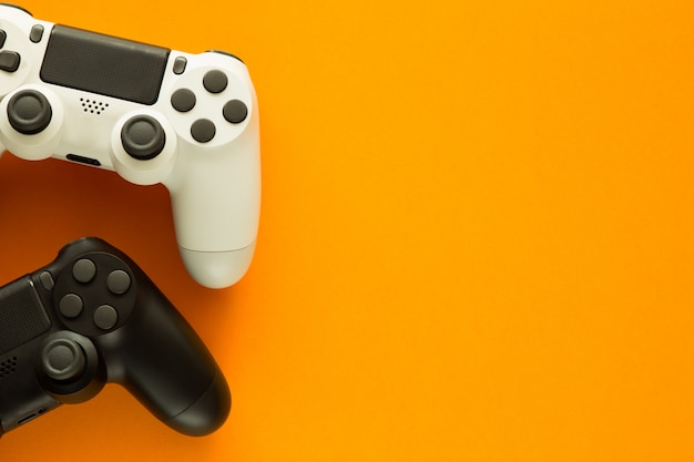 Two gamepads on a yellow table and copy space