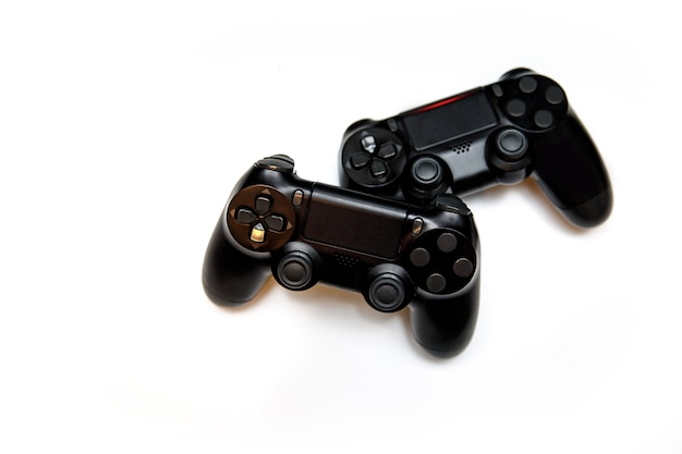 Two gaming controllers for playing video games on white