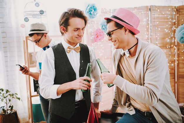 Two gay guys in bow ties clink bottles at party.