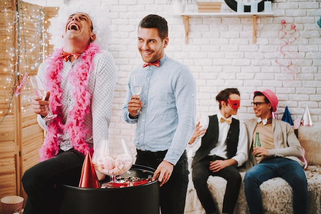 Two gay guys in bow ties playfully flirting at party.