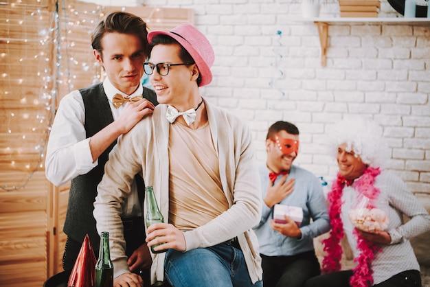 Two gay guys playfully flirting at party