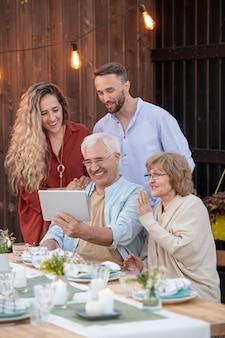 Два поколения смотрят на дисплей планшета во время видеочата