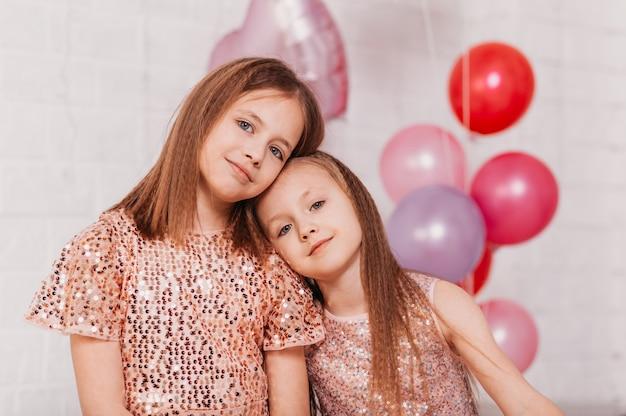 2人の優しい美しい女の子の10代の姉妹が風船のある部屋に寄り添う