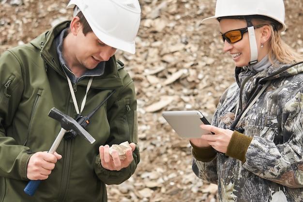 Два геолога исследуют найденный образец минерала.