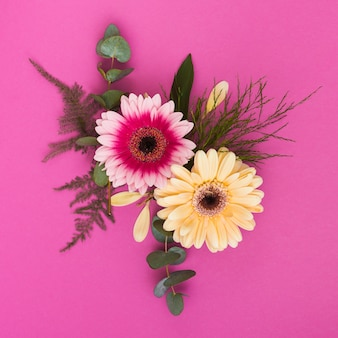 Two gerbera flowers with branches on table