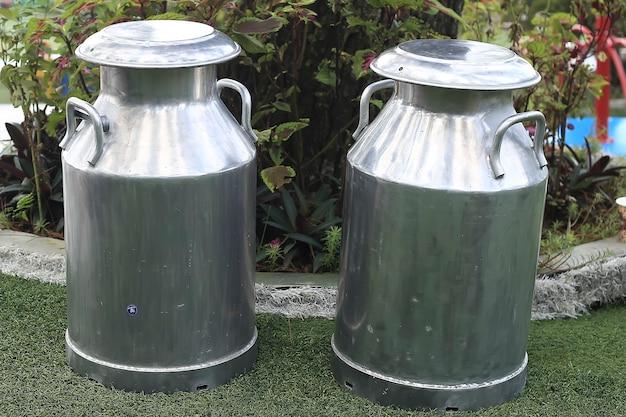 草の上の2つの巨大なミルク缶