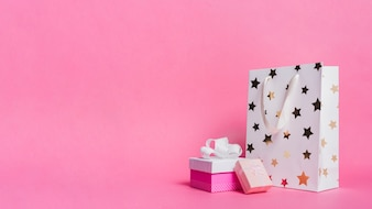 Two gift boxes and white shopping paper bag on pink background