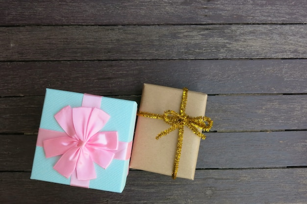 Two gift boxes on the brown wooden background