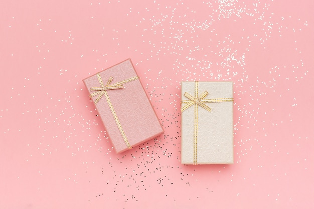 Two gift boxes of pastel colors on pink background, top view