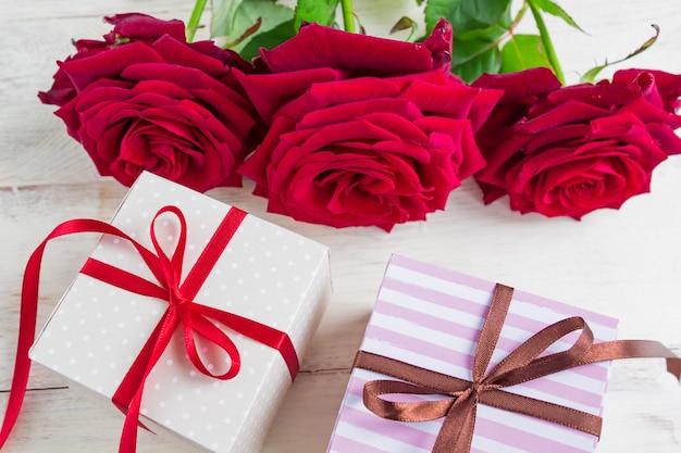 Две подарочные коробки с лентой лук и красивые красные розы на деревянных фоне. открытка на праздник.
