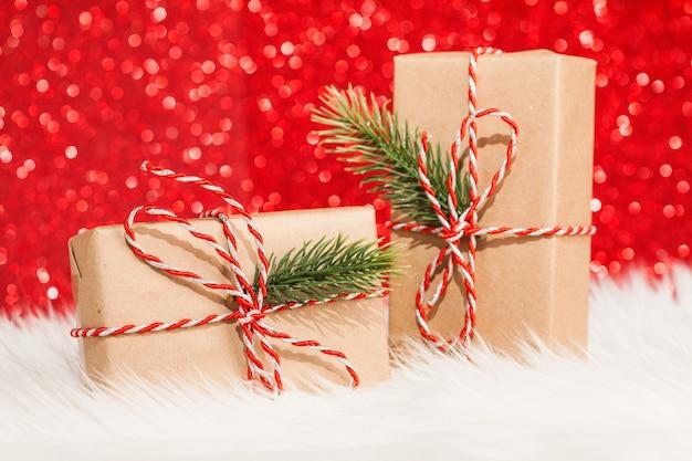 빨간 반짝이 표면에 나무와 두 개의 선물 상자