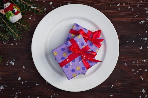 Two gift wrapped in paper with a red ribbon on a white plate
